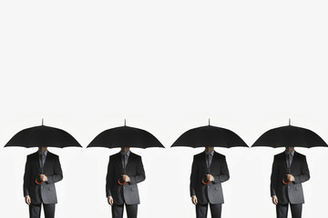 Businessmen holding umbrellas, standing side by side