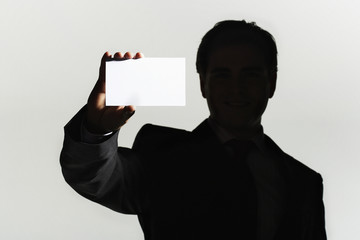 Silhouetted man standing, holding large blank card