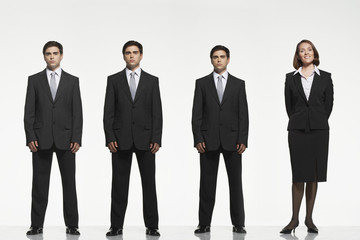 Businesspeople standing side by side, arms by side, behind back