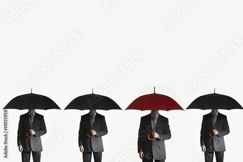Businessmen holding umbrellas, standing side by side, one red umbrella