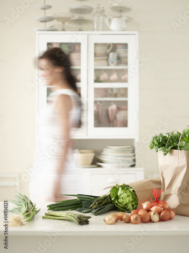 Woman walking behind Fresh Produce on Kitchen Counter, side view