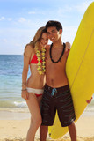 Hawaiian beachboy and blond woman in bikini with surfboard