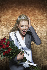 Woman screaming, wearing Employee of the Month pageant paraphernalia, against gold velvet background
