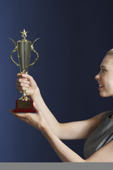 Woman holding and admiring trophy against dark background, profile