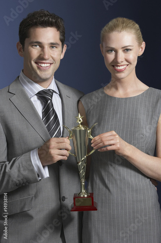 Two business people holding trophy against dark background