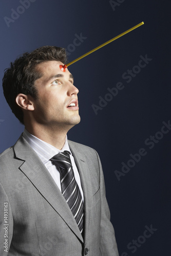 Man with toy arrow in forehead against dark background