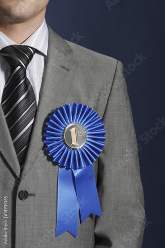 Man wearing blue ribbon on lapel against dark background, mid section