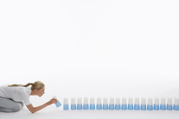 Woman lining up plastic cups on ground against white background