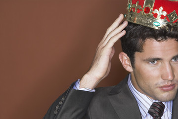 Man putting on crown against brown background, close-up