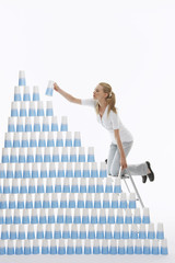 Woman kneeling on ladder to stack plastic cups into pyramid against white background