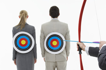 Two business people with targets on backs while man aims bow and arrow close-up of hands, against white background