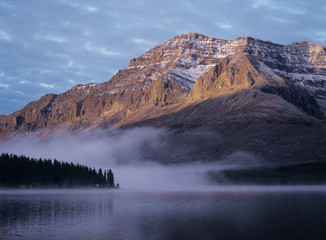 Rocky mountain, fog over lake, sunset
