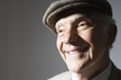 Senior man in flat cap, close up, in studio