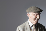 Senior man in flat cap, head and shoulders, in studio