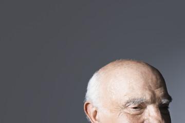 Balding senior man, high section, in studio