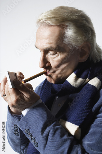 Senior Man wearing suit and lighting cigar in studio