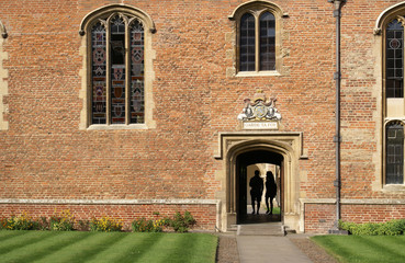 Couple of students passing through doorway to Magdalene College