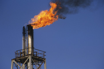 flames rising out of smoke stack
