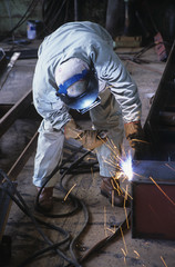 Welder bending down, welding at Work