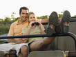 Couple sitting in jeep, woman holding binoculars