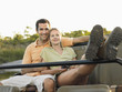 Couple sitting in jeep, woman leaning legs up