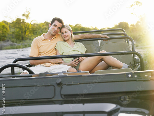 Portrait of couple sitting in jeep