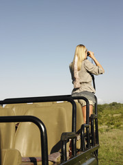 Young woman on safari, standing in jeep, looking through binoculars, back view