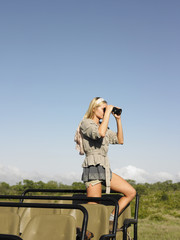 Young woman on safari, standing in jeep, looking through binoculars, side view