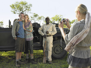 Couple and safari guide posing by jeep, young woman taking photograph