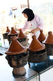 muslim woman cooking food in tagine morocco poster