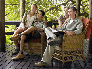 Two couples sitting on terrace, smiling, one holding book