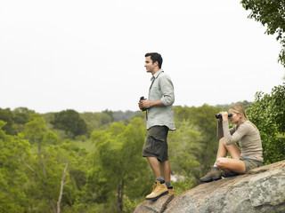 Man and woman on rock, looking at view with binoculars