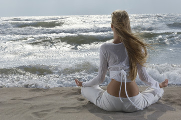 Young woman meditating on beach, facing ocean, back view
