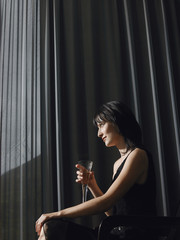 Woman holding champagne in front of curtains indoors, side view