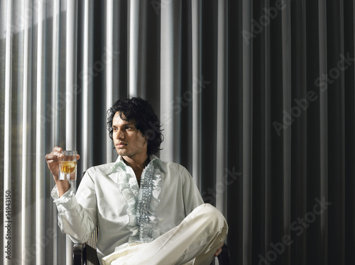 Man sitting with alcoholic drink in front of curtains