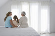 Grandmother, mother and daughter sitting on bed in bedroom