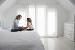 Mother and daughter sitting on bed in bedroom, side view