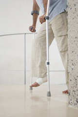 Injured man with wrapped ankle on crutches, low section