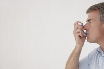 Mature man using inhaler, profile