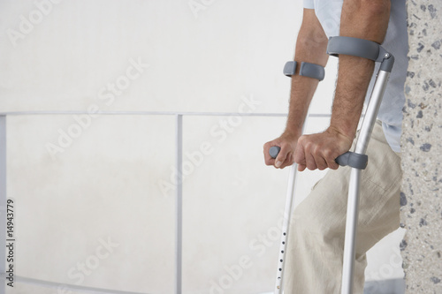 Mid-adult man on crutches, mid section, side view