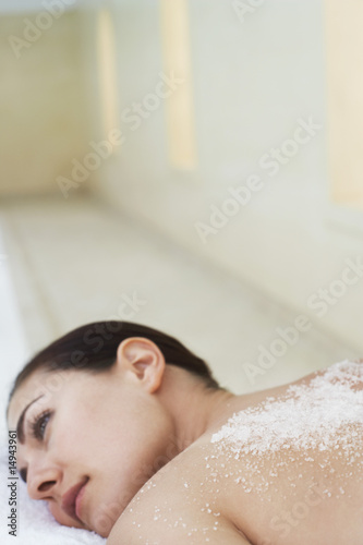 Young woman with salts on back lying on massage table, portrait