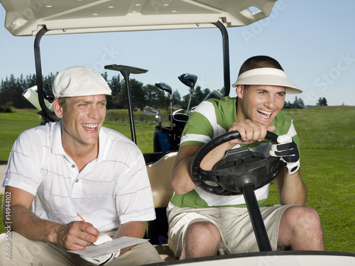 Two young male golfers sitting in cart, laughing