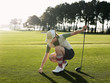 Young female golfer placing ball on tee