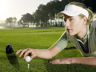 Young female golfer lying on court, placing ball on tee