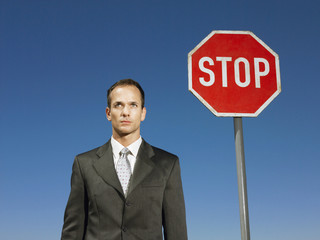 Businessman standing next to stop sign, half length