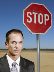 Businessman standing next to stop sign in desert, head and shoulders
