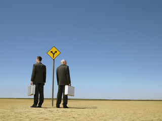 Two businessmen with briefcases standing by road sign in desert, full length, back view