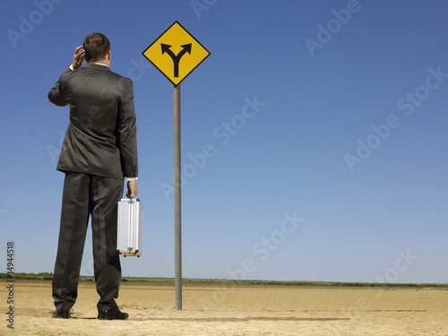 Rear view of confused businessman looking at desert road sign