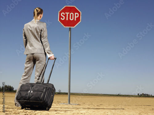 Businesswoman in Desert Looking at Stop Sign