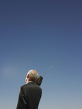 Businessman Under Clear Sky Listening to Radio